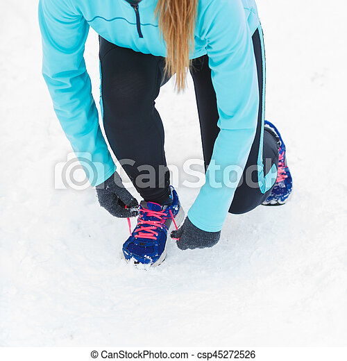 Winter sports fashion concept. Tying sport fitness shoes in snow, footwear for workout outside