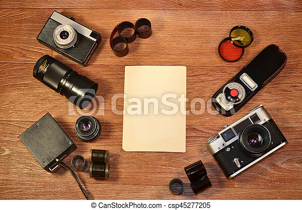 Retro camera and some old photos on wooden table. Vintage mock up for artwork or logo design presentation with film camera and lens. View from above