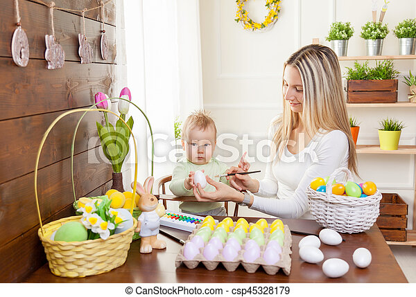 Easter concept. Happy mother and her cute child getting ready for Easter - csp45328179