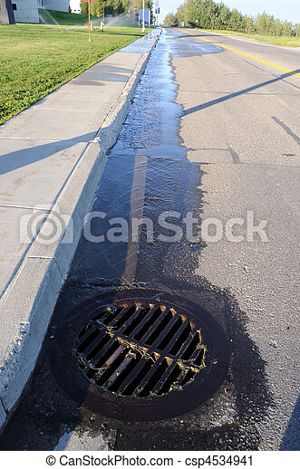 Water Pouring into Street Storm Drain - csp4534941