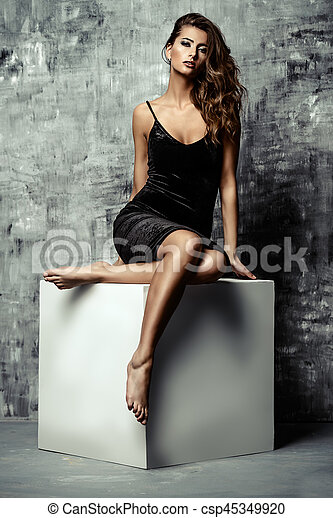 Beautiful sexual woman in black dress posing on a white cube. Femininity. Beauty, fashion and cosmetics concept.
