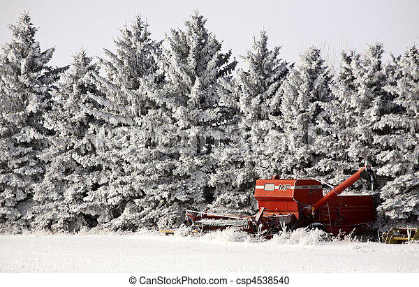 Old combine next to hoar frost covered trees in winter - csp4538540