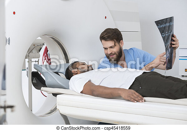 Young male doctor showing X-ray to patient lying on CT scanner at hospital