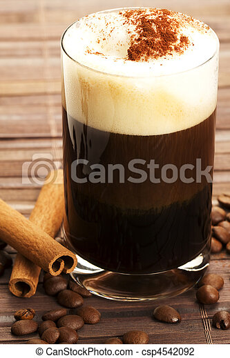 espresso in a straigt glass with milk froth cocoa powder, cinnamon sticks and coffee beans aside on wooden background - csp4542092