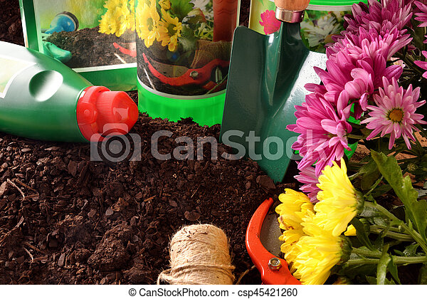 Bottles and containers of gardening products for the growth of plants on soil. With flowers and plants of decoration. Elevated view. Horizontal composition