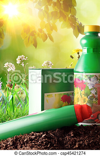 Bottles and containers of gardening products for the growth of plants. With flowers and plants of decoration and green background of nature and sunlight. Front view. Vertical composition
