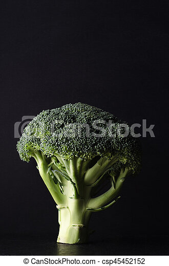 A head of broccoli, tree shaped and standing upright on black surface against black background. Dark , moody lighting.