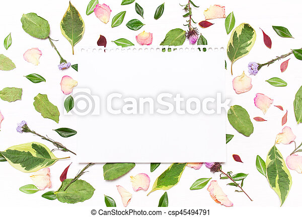 a sheet of paper for text in a frame of flowers, petals and green leaves on a white background.Inspirational image.Type flat, top view