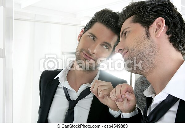 Handsome narcissistic young man looking in a mirror  - csp4549883