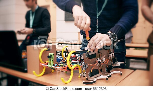 Young man repairing small robot