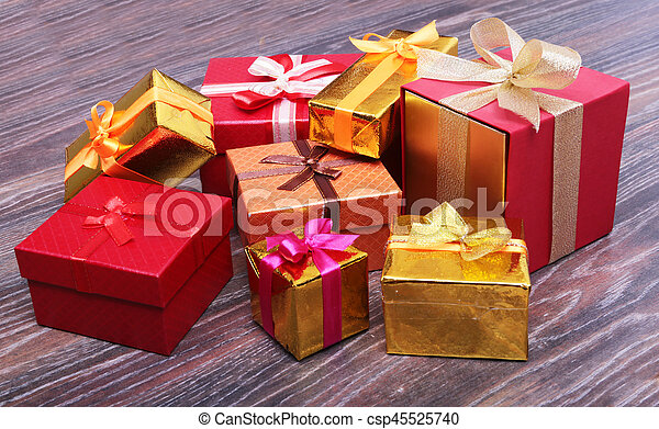 Beautiful gold present box with red bow and ribbons on red backgound.