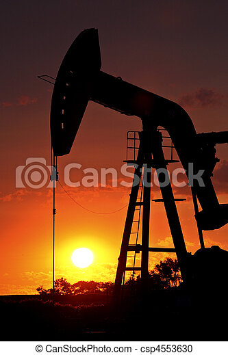 Oil rig pump jack silhouetted by setting sun - csp4553630