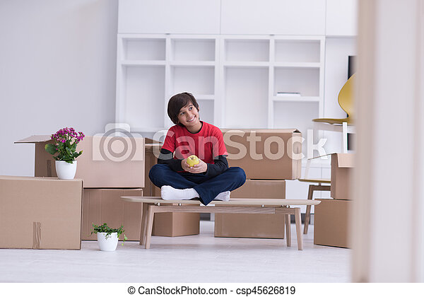 boy sitting on the table with cardboard boxes around him - csp45626819