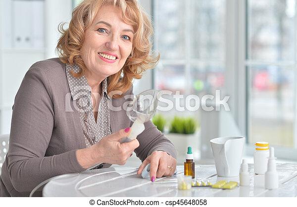 Elderly woman doing inhalation - csp45648058