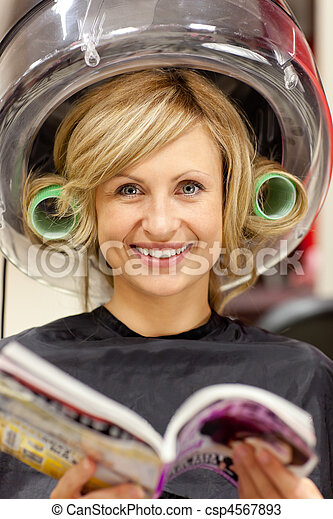 Delighted woman reading a magazine with hair curlers under a hairdryer in a hairdressing salon - csp4567893