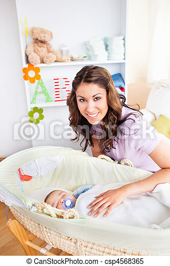 Attentive young mother taking care of her adorable baby - csp4568365