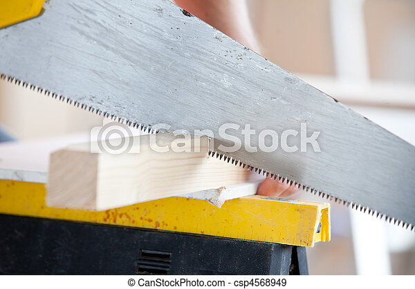 Close-up of a worker sawing a board - csp4568949