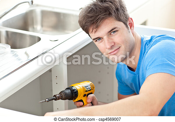 Handsome man holding a drill repairing a kitchen sink - csp4569007