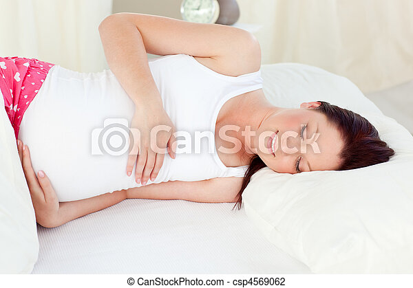 Smiling pregnant woman resting in her bed in the bedroom - csp4569062
