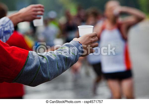 Runner take a water in a marathon race - csp4571757