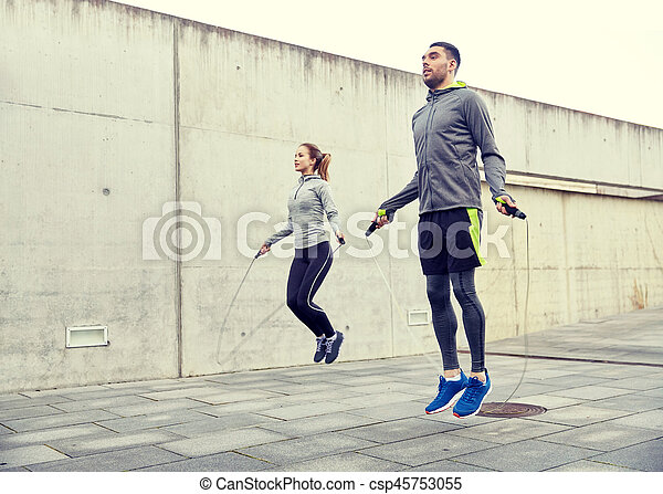 man and woman exercising with jump-rope outdoors - csp45753055