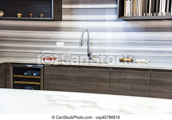 Far shot of blurred modern kitchen sink area with white counter top in front, kitchen with full back splash, kitchen with dark cabinetry and food on beautiful granite counter tops, urban new sink and faucet.