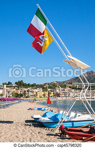 travel to Italy - Italian and Sicilian flags over urban beach of Giardini Naxos town in Sicily in morning