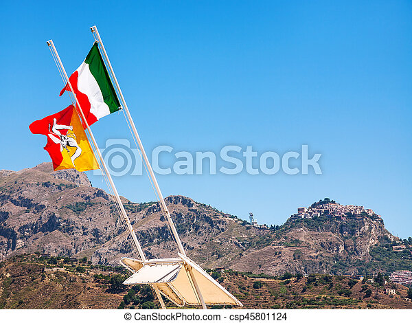 travel to Italy - Italian and Sicilian flags flutter by wind and view of Taormina town on mountain in Sicily