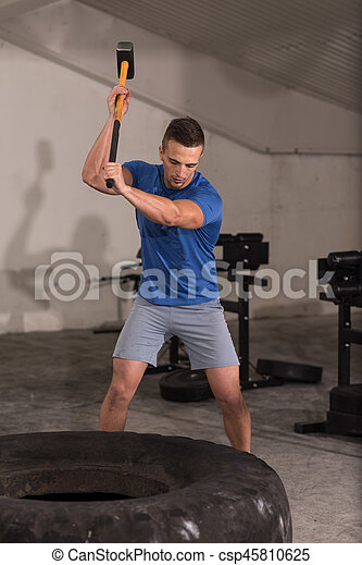man workout with hammer and tractor tire - csp45810625