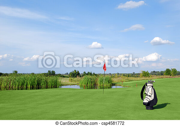 golf field with red flag and bag