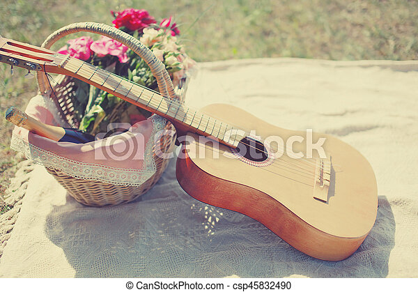 Romantic photo guitar, basket with wine, bouquet flowers on plaid. Romance, love, date, Valentines day concept