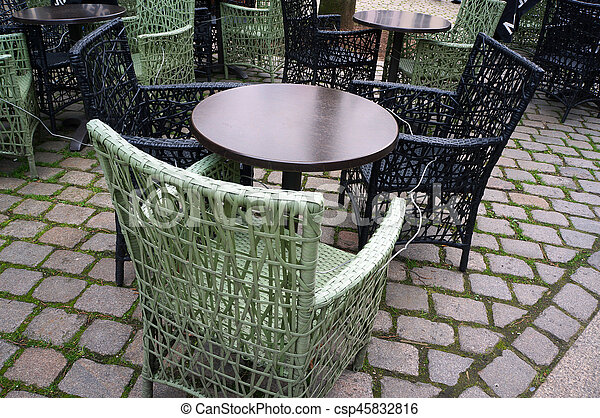 Cafe circle tables and wicker chairs outside on street pavement.