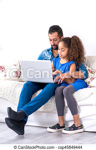 A young black father siting together with his daughter on the couch while they are using a laptop