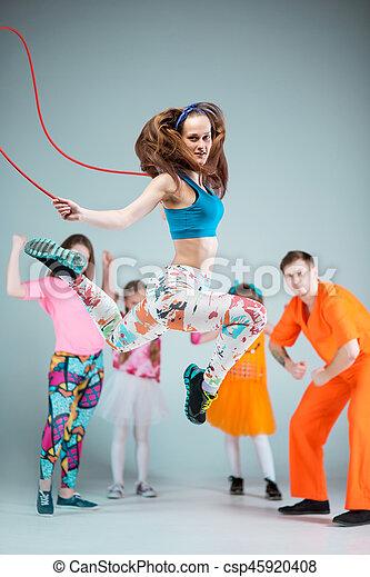 Group of man, woman and teens dancing hip hop choreography and posing at studio on gray