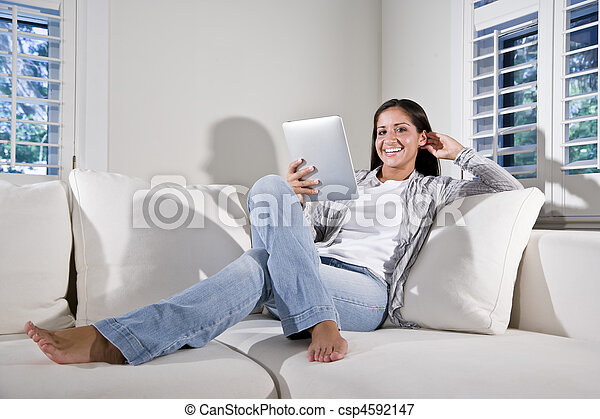 Hispanic woman reading electronic book on couch - csp4592147