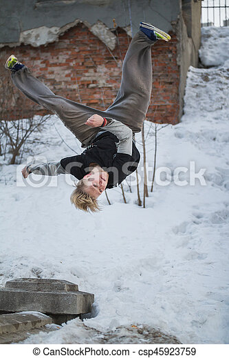 Backflip parkour in winter snow park - blonde hair teenager, vertical