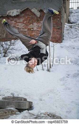 Backflip parkour in winter snow park - blonde hair teenager, vertical