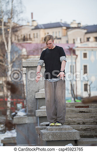 Parkour in winter park - blonde guy teenager ready for acrobatic jump - flip, telephoto
