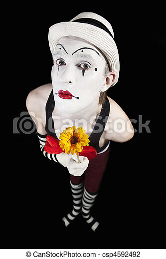 Funny mime in white hat with a bouquet of flowers on a black background - csp4592492