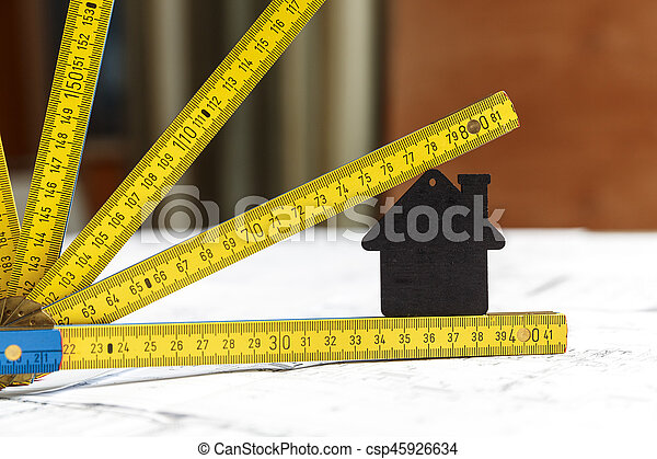 Image of small black toy house and a collapsible yellow and blue ruler standing on top of architecture blueprint plan