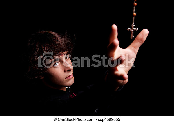 young men with arm raised, trying to grab a crucifix, isolated on black, studio shot - csp4599655