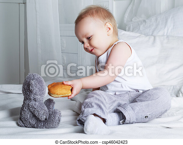 baby in bed at home with a bun