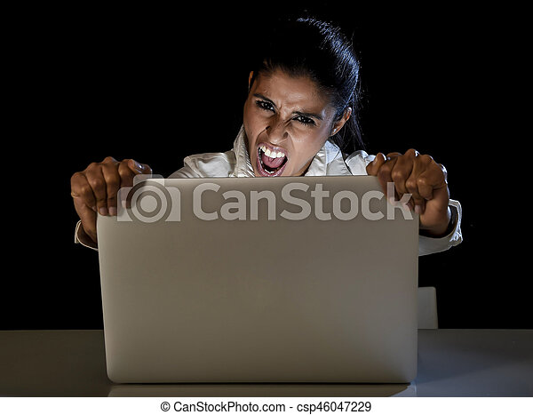 young business woman or student girl working in darkness on laptop computer late at night holding the screen angry in stress and upset in long hour of work concept isolated on black background