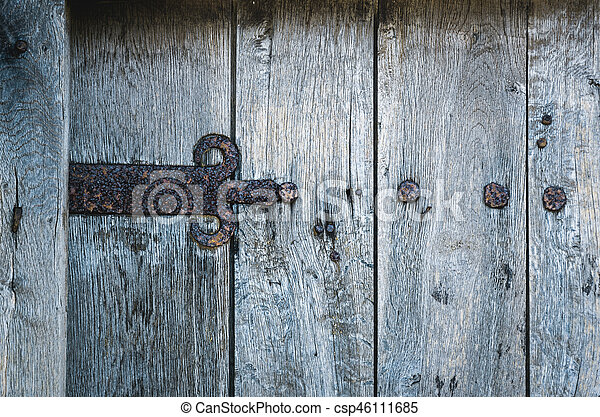part of old wooden gate with rusted iron hinge - csp46111685