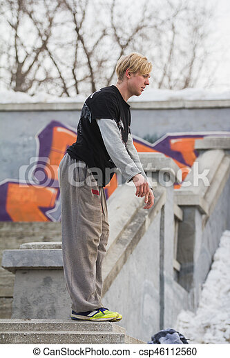 Parkour in park - blonde guy teenager ready for acrobatic jump - flip, telephoto