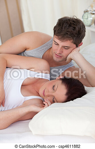 affectionate young man looking at his pregnant wife sleeping both lying on the bed at home - csp4611882