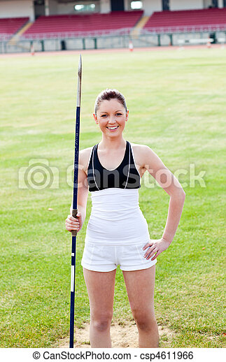 joyful sporty woman holding a javelin standing in a stadium - csp4611966