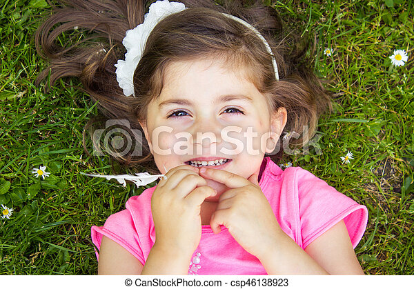 Little girl laying in the grass - csp46138923