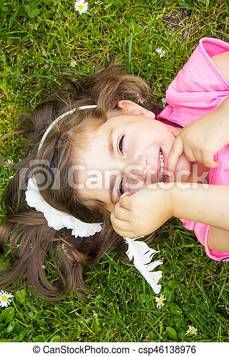 Little girl laying in the grass - csp46138976
