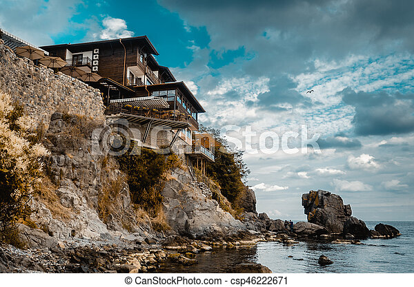 lonely old house on a rock cliff on seashore - csp46222671